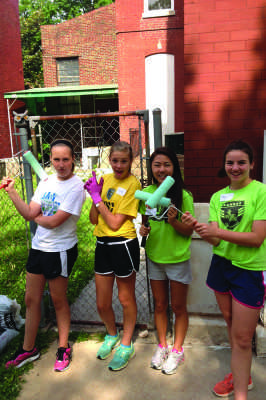 Sophomore Abby Yi (second from right) and her fellow volunteers  repainted the children's center 's fading and chipping exterior.  Along with painting, the volunteers also gardened the overgrown plants.