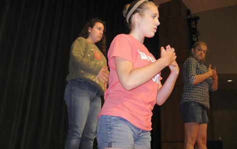 Choreographer Tori Loepp checks her dancers as they run through their 'Jungleland' dance.