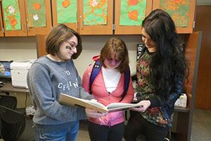 Peer tutors sophomore Izabella Borowiak-Miller and senior Morgan Cowles read with freshman special education student Sydney Ross.