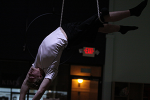 Senior Andrew Woods situates his right leg in a rope for support and drapes his back over the trapeze bar.