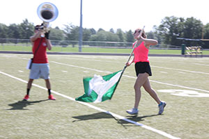 Junior Charlee Striebinger holds her flag strong as she strides across the field.