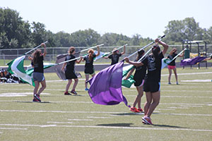 The guard girls gracefully swing their flags over their heads.