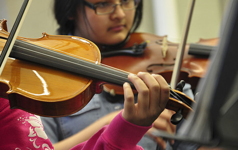 Sophomore Amira Bajracharya practices her violin with the Pit Orchestra in preparation for the musical.