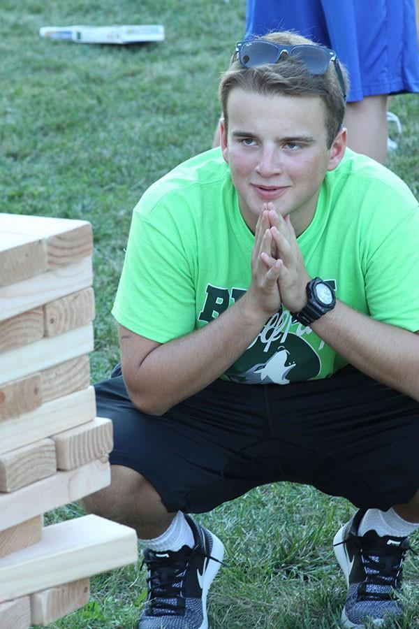 Junior WPC member Ryan Davis carefully observes the Jenga tower before making his move.