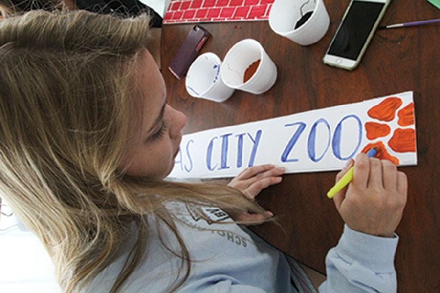 """Helping out at the homecoming work day, senior Kathryn Venzon paints a sign that says """"Kansas City Zoo."""" This sign was included in the front entryway at the dance."""