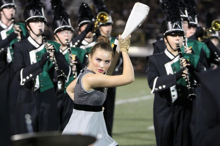 Twirling her rifle, sophomore Claire Boomer performs in the halftime show at the football game on Sept 25. Boomer is a part of the Color Guard, which performs and competes with the band.