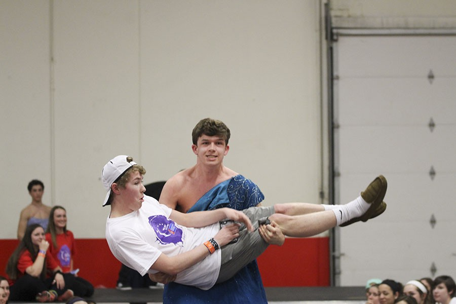 Carrying senior Harrison Carney, senior Will Hawkins participates in the talent portion of the Mr. Relay contest. Hawkins's talent in the beauty contest was weightlifting.