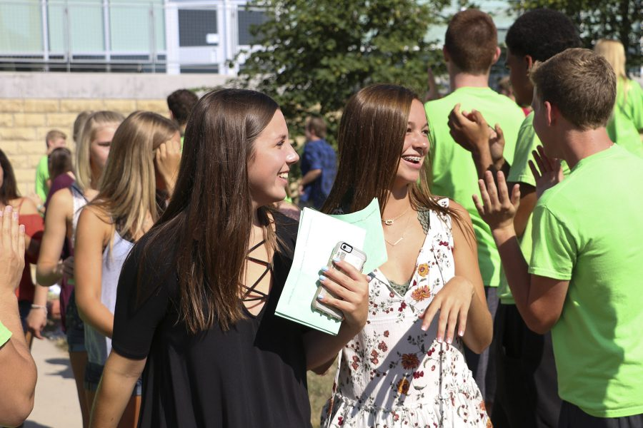 Freshman students walk through the courtyard while mentors and staff clap for them.