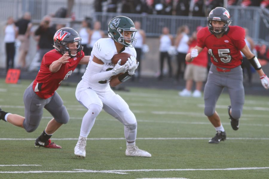 Number 21 senior Daniel Foulon catches the ball in the first quarter for a first down.