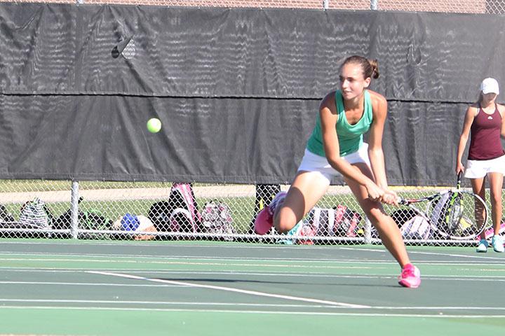 Swinging her racquet, senior Josie Henzlik runs to the ball.