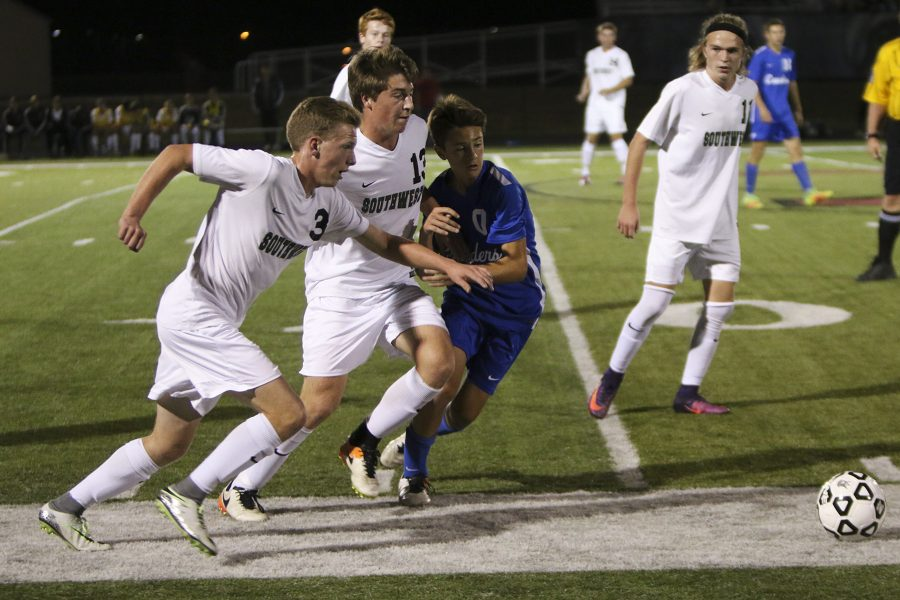 Number three junior Cole Petri and number 13 senior Brady Dow fight an opponent to gain control of the ball.