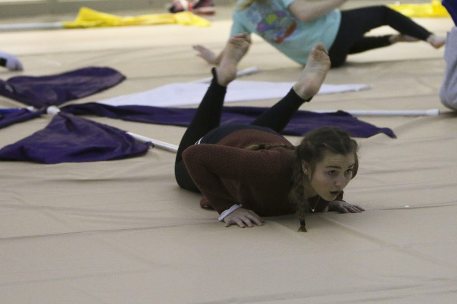Doing floor work, junior Claire Boomer rolls and looks ahead to watch her fellow winter guard members.