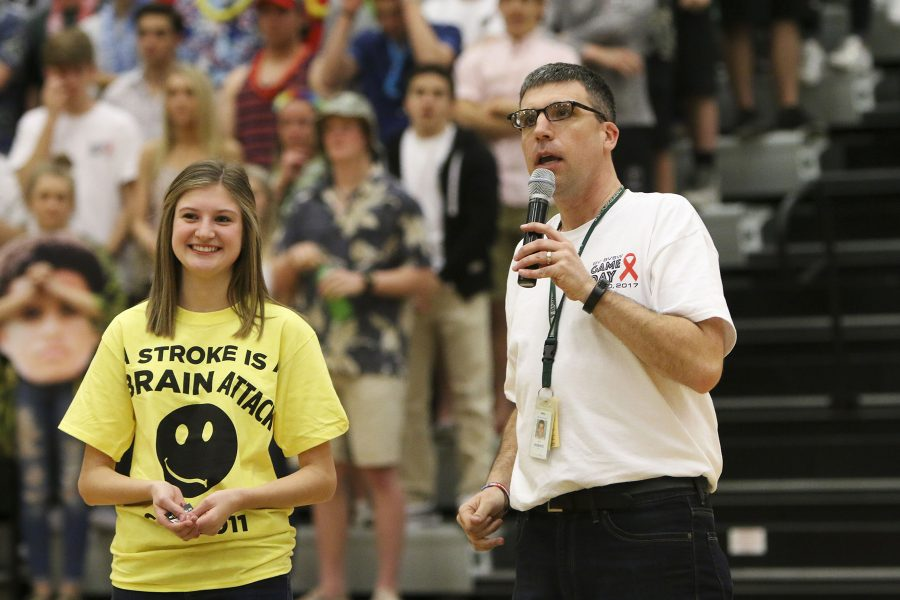 Principal Scott Roberts tells the crowd at the game how to recognize the signs of a stroke.