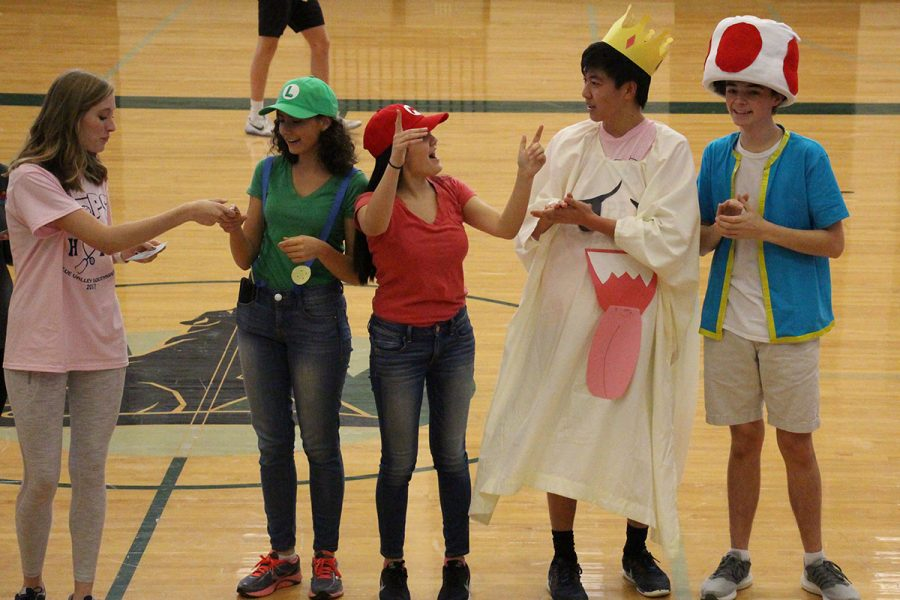Team+Mario%2C+seniors+Rachel+Holzer%2C+Sumaya+Hussani+and+Nick+Castle+and+junior+Ted+Shi%2C+accepts+the+prize+for+best+costume+from+senior+Evie+Peterson.
