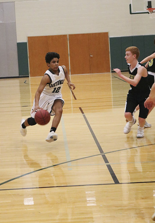 Dribbling+down+the+court%2C+freshman+Cortez+Dyson+drives+toward+the+basket+to+try+and+tie+up+the+game.