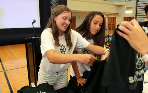 Organizing the Green and White T-shirts, senior Kori Stonestreet prepares for the third assembly of the year. WPC members planned and put on the assembly on Aug. 24.