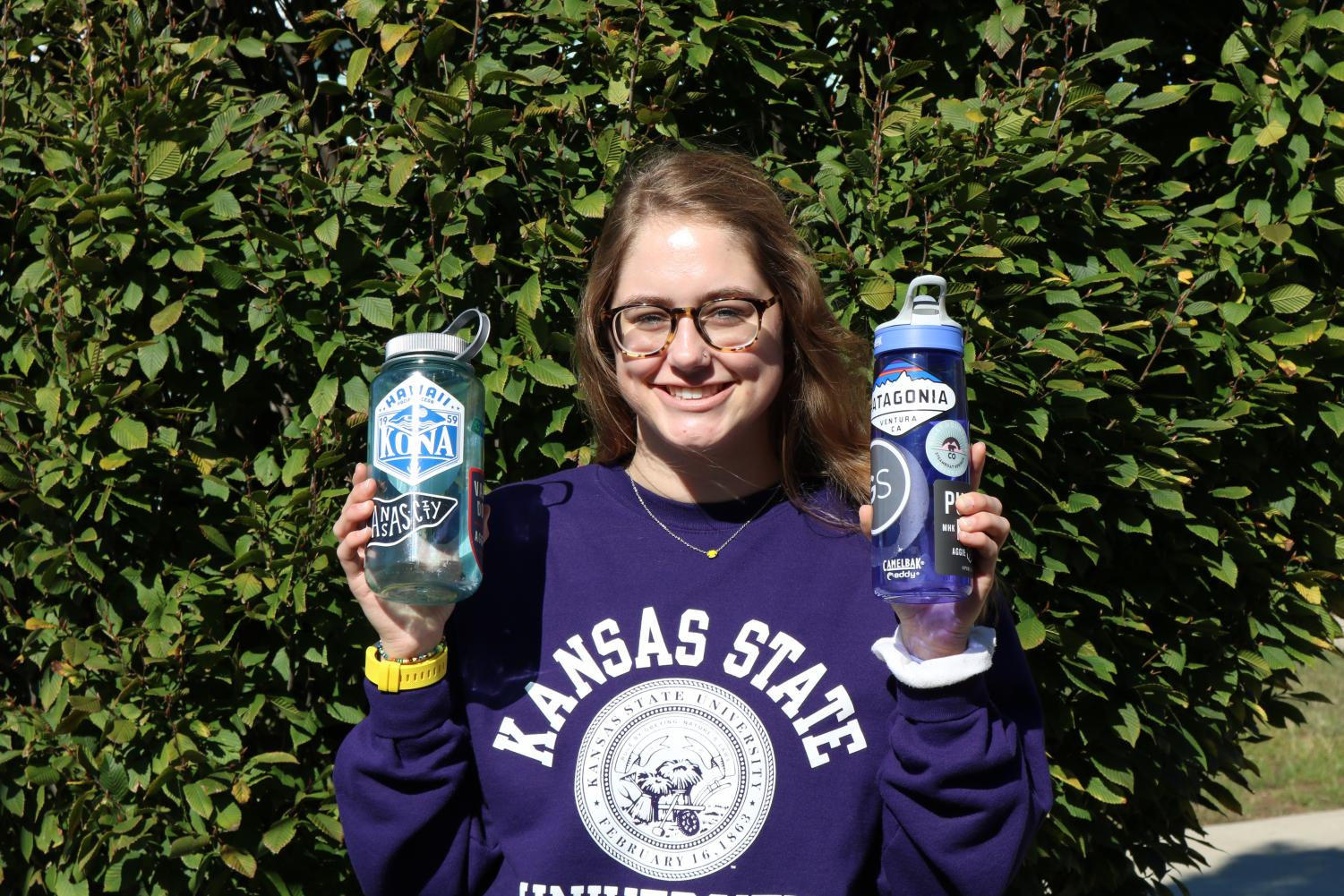 Savannah Greathouse flashes her two favorite water bottles. These stickers represent her favorite things, ranging from the outdoors to her favorite brands.