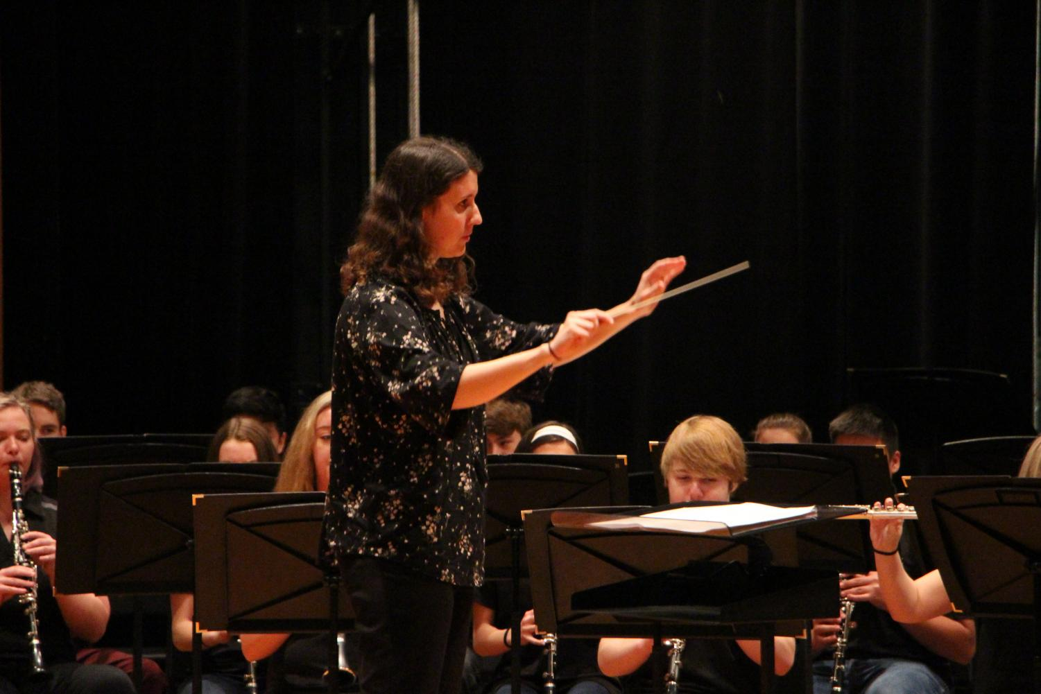 With arms lifted, assistant band director Laura Bock conducts her students. She conducted the band through two songs at the band festival on Thursday April 4.