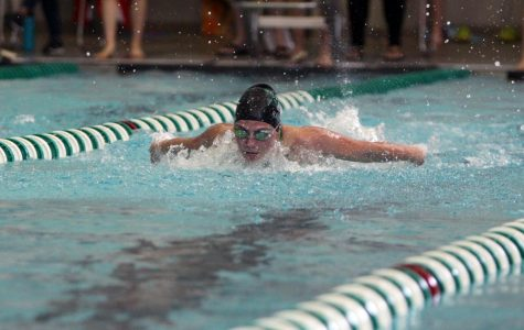 Pulling her arms around, junior Emerson Ralston comes up for air while swimming butterfly.