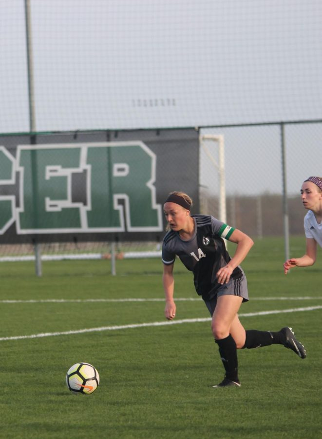 Running to the ball, senior Calista Schechinger beats the defender to gain possession over the ball.