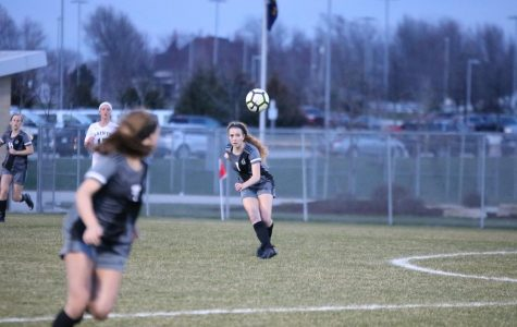 Eyes on the ball, sophomore Ashley Lamfers clears it across the field.