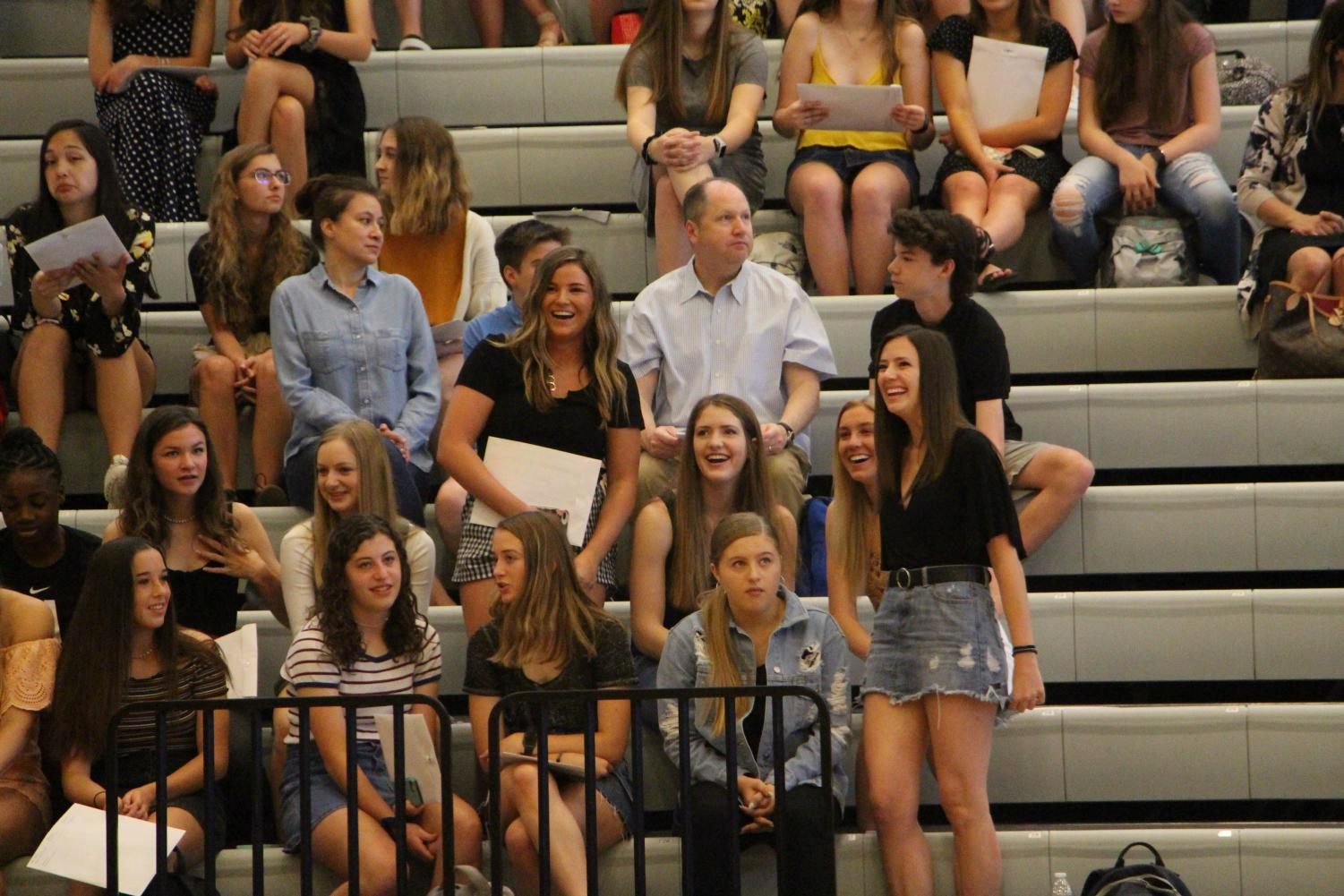 After being recognized for their successes, Brooke Davis and Carson Craft laugh in the bleachers.