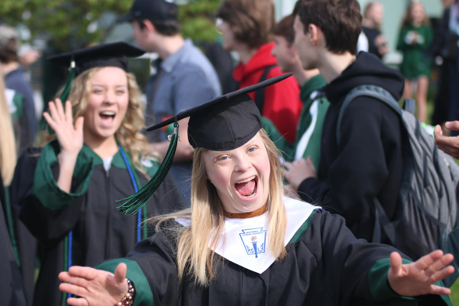 Smiling to her friends, senior Violet Holman finishes the tradition of walking through courtyard.