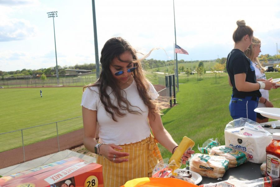 As she prepares her food, sophomore Victoria Lazo de la Vega puts mustard on her hotdog.