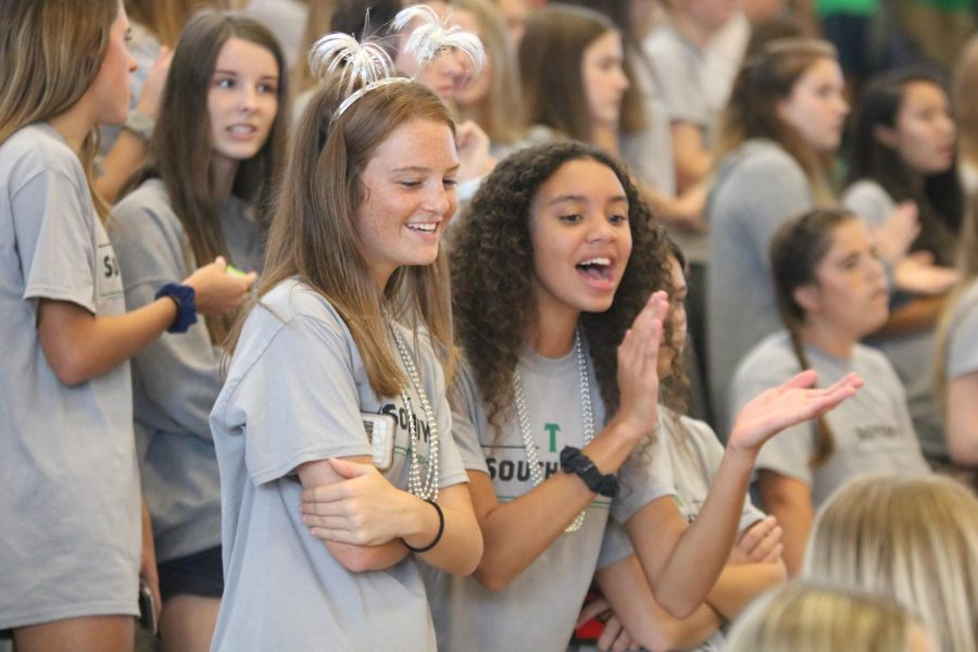 Sophomores Tamerra Gantt and Hunter Hartwegar cheer on the fall sports teams from the bleachers during the Fall Sports Assembly on Sept. 20.