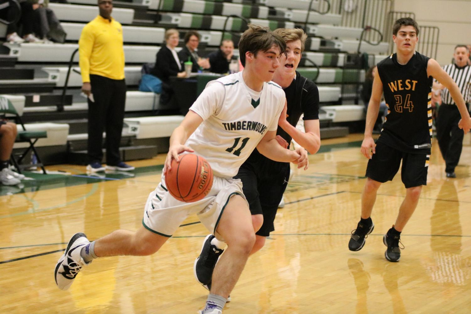 Sophomore Tyler Sardelli battles for the ball at the boys basketball game.