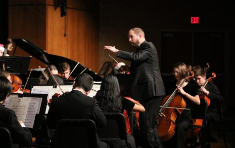 Orchestra director Ethan Loewen moves his hands while conducting a piece for the orchestra quarterly concert.