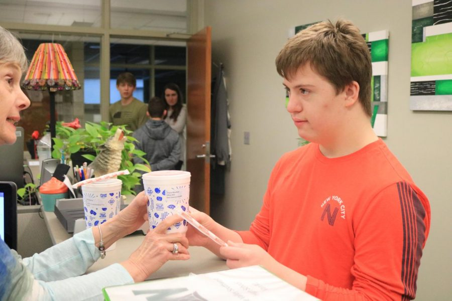 Junior Gabi Ricci delivers a Sonic drink to athletic administrative assistant Diane Murdock.