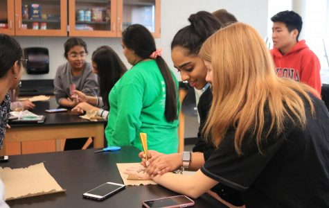 Sophomore Ellie Philips looks over as sophomore Evanna Dominic squeezes henna onto her hand. Photo by Rebecca Suku.