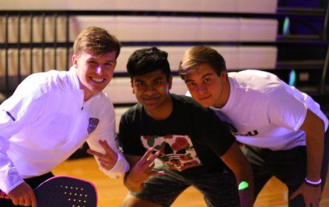 Senior Maclain Petri, Junior Karthik Satish and Senior Jake Traen smile on the court.