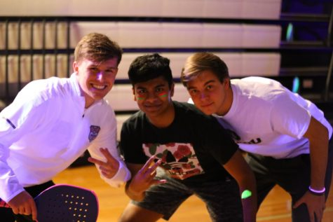 Senior Maclain Petri, Junior Karthik Satish and Senior Jake Traen smile on the court.