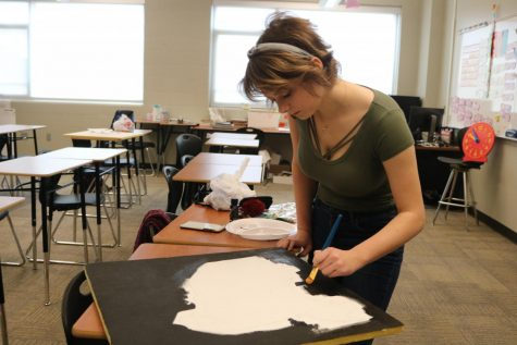Junior Olivia Palmer fills in the background of her painting of China.