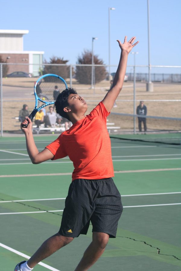 Getting ready, freshman Vishal Rajkumar serves the ball at practice on March 5. The tennis team competed in a pre-season tournament before spring break. Photo by Sydney Wilson.