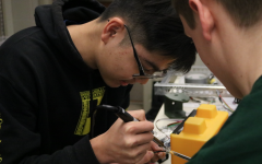 Senior Andrew Jin focuses on repairing the robot in his drafting class.