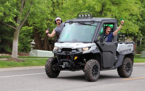 Hands out the window, seniors Stefan Freeman and Michael Paule ride on a Polaris during the parade on May 17. The parade took place on what would have been graduation day, which was postponed due to the COVID-19 pandemic. Photo by Lianna Shoikhet.