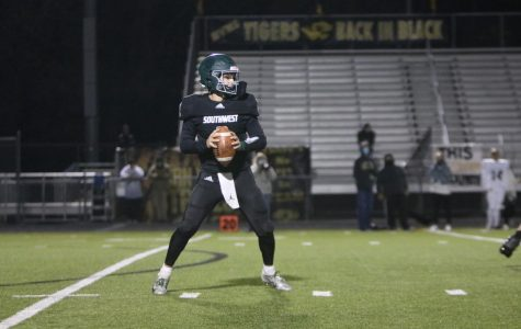 On Oct. 16, senior Tanner Curry decides who to throw the ball to at the varsity football game against Blue Valley High.