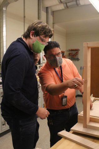 Teacher Steven Cortez helps junior Jackson McCarty add the finishing details to his desk.