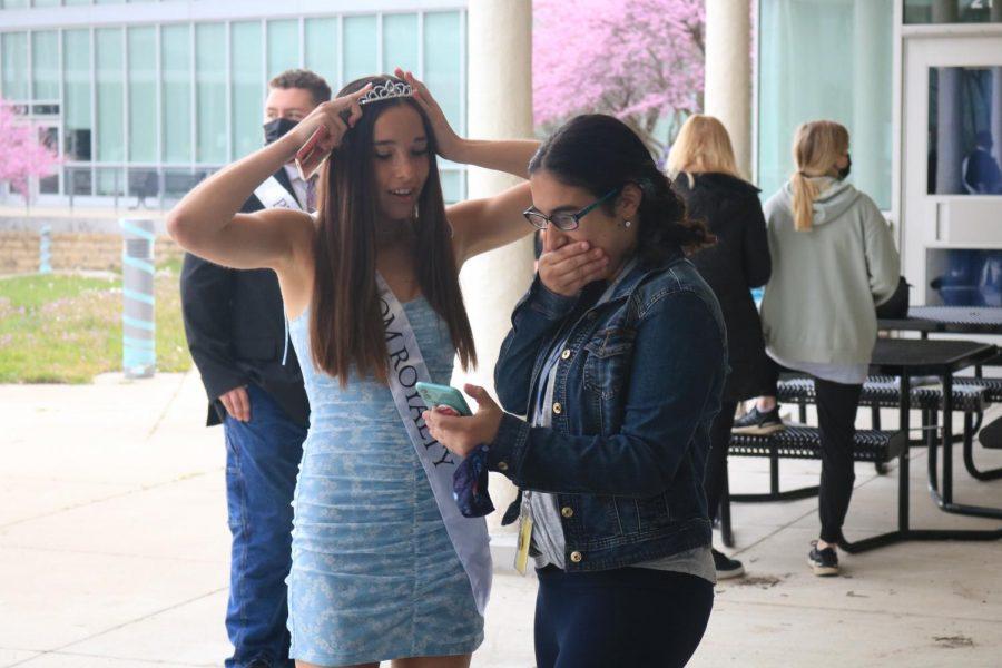 Senior Jaylie Hicklin looks at photos with junior Monica Hura.