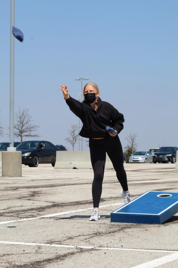 Focused on the bean bag, freshman Taylor Renzi plays in the cornhole tournament on April 24.