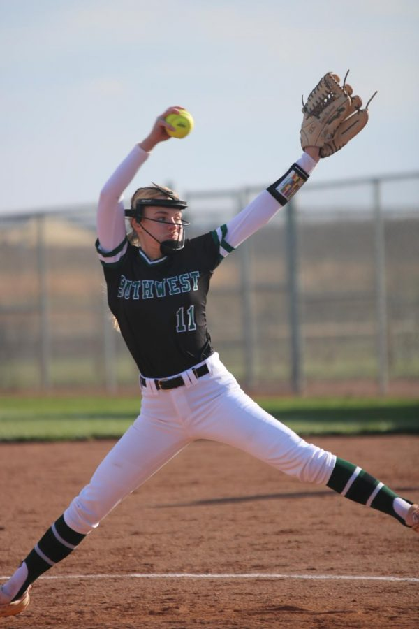 Sophomore Sophie Brickman leaps forward and swings her arm to pitch the ball.