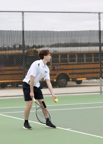 In the JV tennis match on March 24, Senior Matthew Young prepares to serve the ball to his opponent.