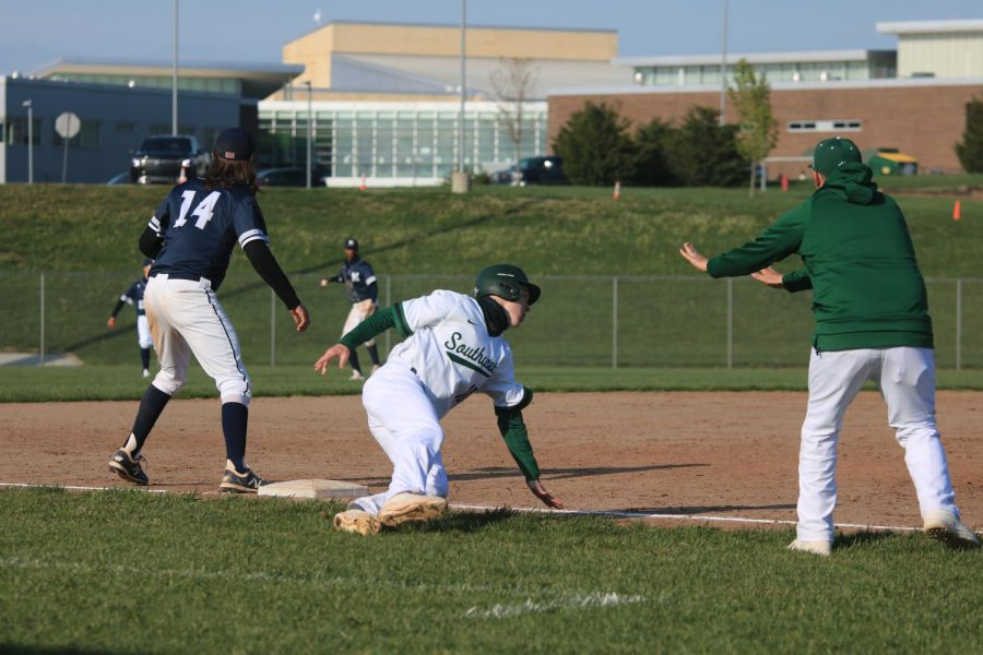Signaled to stay at third from coach Dustin Barnes, junior Kaden Moore fights to stay safe.