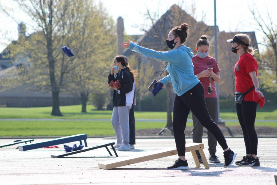 Looking ahead, junior Sutton Cotsworth lets go of her cornhole bag at Cornhole for a Cure on April 24, 2021. Participants were encouraged to donate to help raise money for the Oncology fund at Children's Mercy.