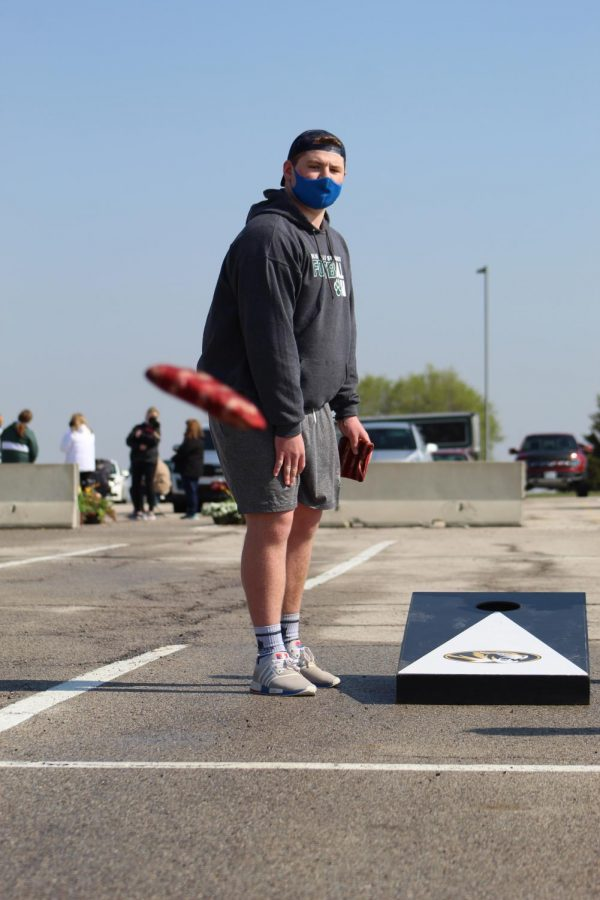 Eyes on the bag, junior Andrew Farrell watches his cornhole bag land on the board at Cornhole for a Cure on April 24, 2021. Farrell competed with senior Hayden Porter as his partner.