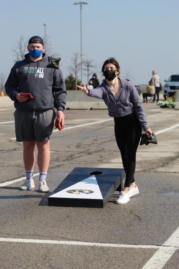 Two bags in hand, senior Lily Spinner throws one of her cornhole bags at Cornhole for a Cure on April 24, 2021. With the COVID-19 restrictions, Cornhole for a Cure was made as a replacement event for Hoops 4 Hope.