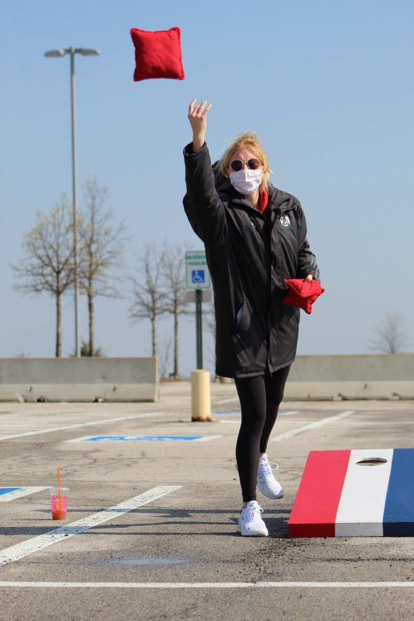 Fingers in the air, senior Merritt Ellis releases the cornhole bag at Cornhole For a Cure on April 24, 2021. Cornhole for a Cure was put on by members of Hoops 4 Hope, Wolf Pack Crew, and Student Council to help in the fight to #CrushKidCancer.